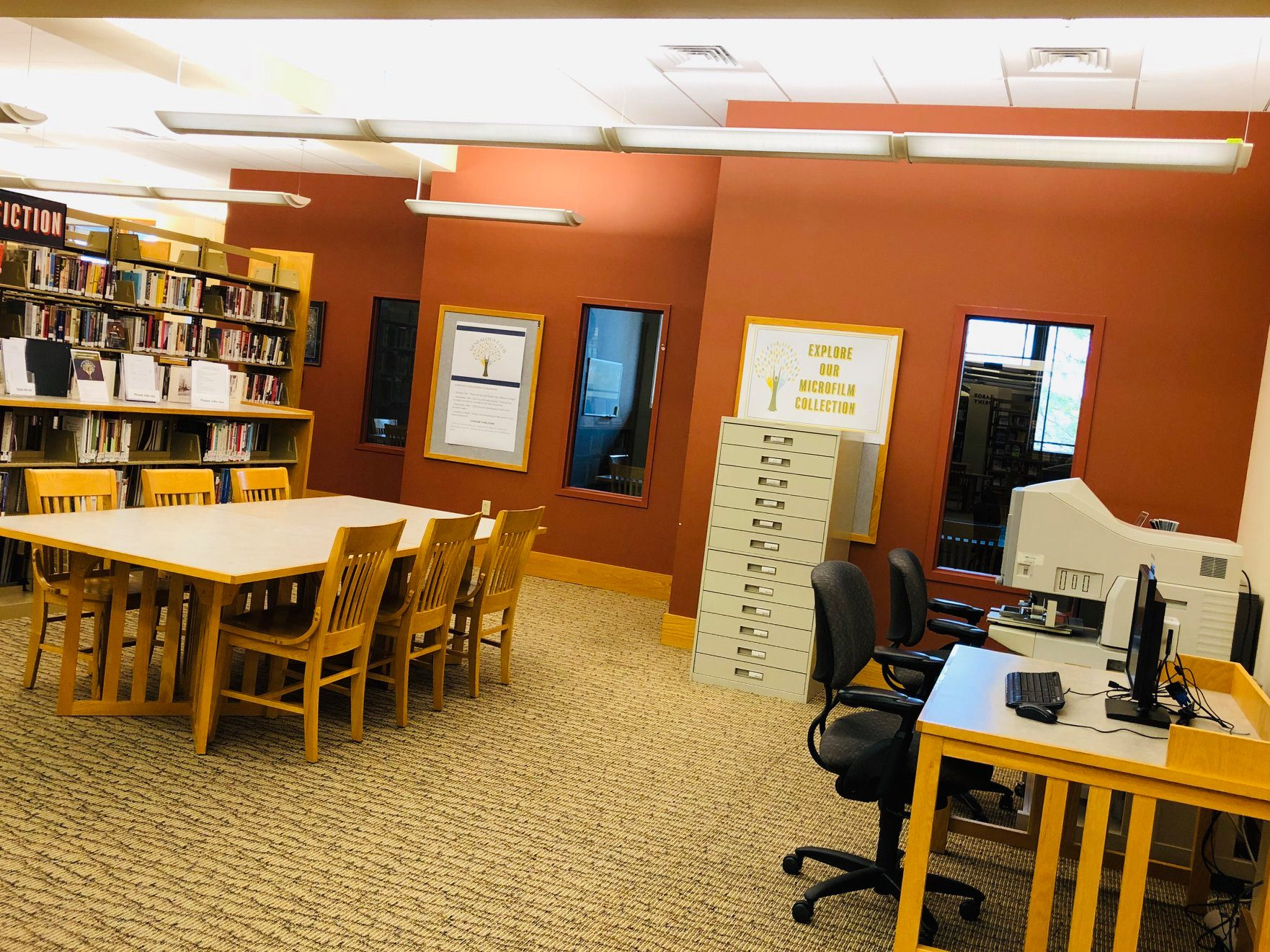 New Genealogy and Local History Area upstairs in front of study rooms. Photo shows area with dedicated computer, microfilm cabinet and reader to the right; study table with six seats in the middle; and low shelves of local history and genealogy books and other resources on the left.